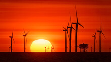 Offshore Wind Turbines With Sun Just Above Horizon