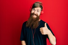 Redhead Man With Long Beard Listening To Music Using Headphones Doing Happy Thumbs Up Gesture With Hand. Approving Expression Looking At The Camera Showing Success.