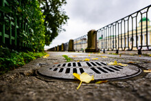 Rainy Autumn Day In The City, An Alley In The Park Running Along The Embankment. Close Up View Of A Hatch At The Level Of Granite Pavement