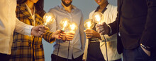 Background With Young Multiethnic Business Team Holding Glowing Vintage Edison Lightbulbs. Multiracial Men And Women Join Shining Electric Light Bulbs For Teamwork And Sharing Creative Ideas