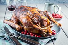 Traditional Christmas Roast Goose With Potatoes, Apple And Cranberry Served As Close-up On A Design Plate