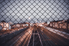 High Angle Shot Of A Cityscape And Rail Tracks Seen Through Metal Mesh Fence
