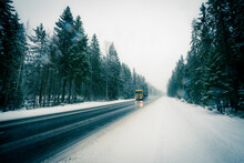 The Truck Is Driving Along The Winter Road During The Snowfall Passing Through The Spruce Forest. View From The Side Of The Road, Image In The Blue Toning
