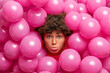 Leinwandbild Motiv Displeased curly haired young woman sticks out head through inflated balloons looks sadly at camera expresses negative emotions being in bad mood. Party decorations concept. Spoiled holiday.