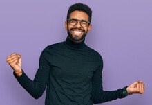 Young African American Man Wearing Casual Clothes Very Happy And Excited Doing Winner Gesture With Arms Raised, Smiling And Screaming For Success. Celebration Concept.
