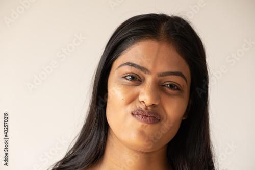 фотография Closeup shot of a doubtful Asian girl on a white background