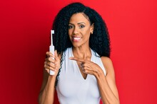 Middle Age African American Woman Holding Electric Toothbrush Smiling Happy Pointing With Hand And Finger