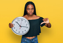 Young African American Woman Holding Big Clock With Angry Face, Negative Sign Showing Dislike With Thumbs Down, Rejection Concept