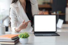 Close-up Of A Businesswoman Hand Pointing At A Tablet A Blank White Screen At The Office. Mock Up.