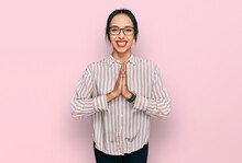 Young Hispanic Girl Wearing Casual Clothes And Glasses Praying With Hands Together Asking For Forgiveness Smiling Confident.
