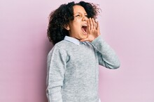 Young Little Girl With Afro Hair Wearing Casual Clothes Shouting And Screaming Loud To Side With Hand On Mouth. Communication Concept.