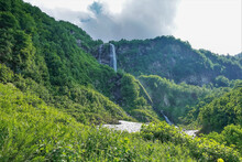 The Mountains Are Covered With Bright Lush Green Vegetation. A Waterfall Flows From The Top To The Valley. A Patch Of Snow At The Foot Of The Cliff. Clouds In The Sky. Caucasus.