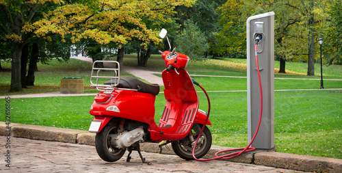 Electric scooter with charging station on a city street  - fototapety na wymiar
