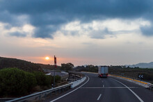Truck Driving On The Highway Next To A Windsock And The Sun Peeking Through The Clouds At Dawn.