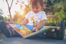 Little Boy With Book Outdoors
