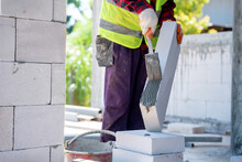Bricklayer Builder Using Cement Mortar To Put The Lightweight Bricks. At Construction Site