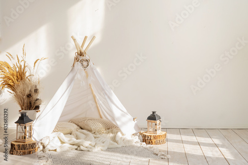 Canvas Print White fabric wigwam and Native American decor in the interior of the children's room with copy space