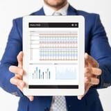 Fototapeta Kawa jest smaczna - Digital tablet with analysis app on screen in businessman hands