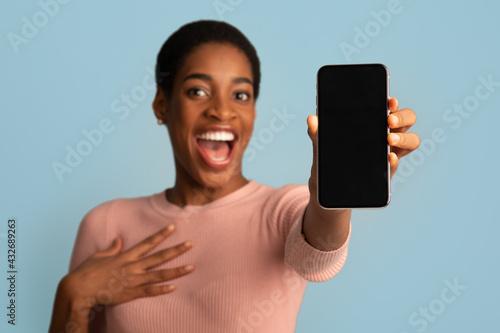 Fototapeta Great App. Amazed African Female Showing Modern Smartphone With Blank Black Screen obraz