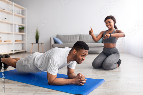 Fit black man standing in plank pose, his girlfriend noting time on smartwatch, showing thumb up gesture at home - fototapety na wymiar