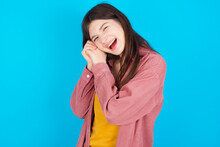 Dreamy Young Beautiful Caucasian Woman Wearing Pink Jacket Over Blue Wall With Pleasant Expression, Closes Eyes, Keeps Hands Crossed Near Face, Thinks About Something Pleasant