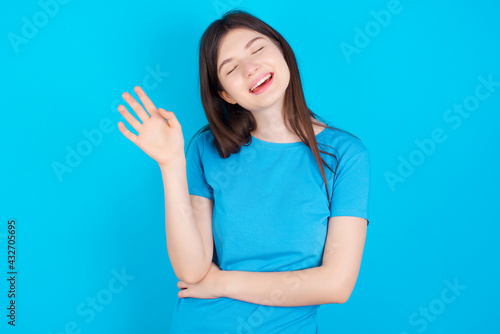 Vászonkép Overjoyed successful young beautiful Caucasian woman wearing blue T-shirt over b