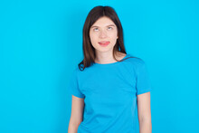 Funny Young Beautiful Caucasian Woman Wearing Blue T-shirt Over Blue Wall Makes Grimace And Crosses Eyes Plays Fool Has Fun Alone Sticks Out Tongue.