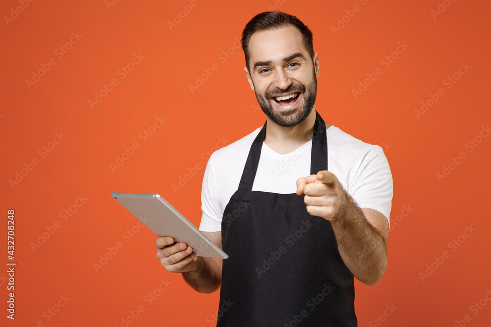 Obraz Young leader man barista bartender barman employee wear black apron white tshirt work in coffee shop using tablet pc computer point finger camera on you isolated on orange background business startup fototapeta, plakat