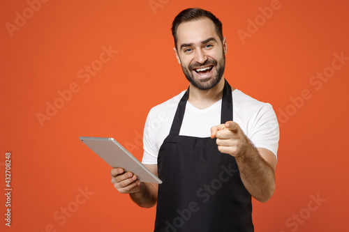 Fototapeta Young leader man barista bartender barman employee wear black apron white tshirt work in coffee shop using tablet pc computer point finger camera on you isolated on orange background business startup obraz
