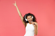 Young Smiling Happy Fun Expressive African American Woman 20s Wear Basic Casual White Tank Shirt Headphones Sing Song In Microphone Point Finger Up Isolated On Pink Color Background Studio Portrait