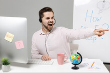 Employee Operator Business Man In Set Microphone Headset For Helpline Assistance Sit Work At Call Center Office Desk With Pc Computer Point Finger Aside Shout Do It Isolated On Grey Background Studio