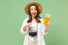 Traveler Tourist Woman In Hat Camera Hold Passport Covid-19 Immune Vaccination Boarding Pass Ticket Isolated On Green Background Passenger Travel Abroad On Weekends Getaway Air Flight Journey Concept