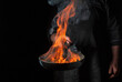 Chef cooking food in pan with fire flame on black background. Restaurant and hotel service concept. Free advertising space