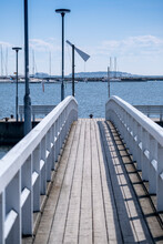 Old Wooden Pier With White Wooden Railings Against The Blue Sea.