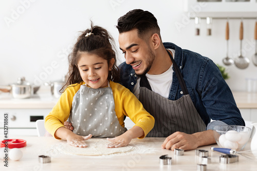 Foto Happy arab father and little daughter baking together in kitchen, preparing past