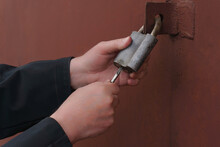 A Man Opens A Large Garage Door Lock With A Key.Close-up