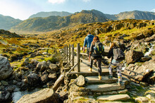 Group Of Hiking Backpackers In Welsh Mountains Walking Over A Bridge.