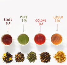 Four Cups Of Tea  On White   Table With Large Assortment Of Herbal, Flower, Berry And Leaf Dry Teas.
