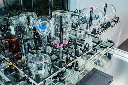 Fototapeta Laboratory glassware washer. Laboratory glassware cleaning process. Laboratory glassware on metal stand. Lab dishwasher. Machine for sterilizing test tubes in lab. Cleaning lab flasks. obraz