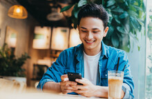 Young Asian Man Sitting And Using Smartphone At Coffee Shop