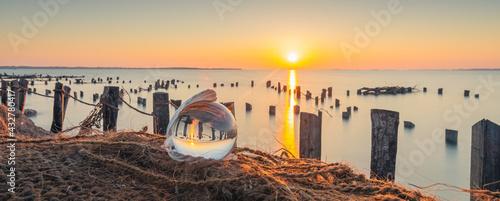 Fotografie, Obraz Vue d'une boule de cristal dans un coquillage sur un filet de pêcheur avec un coucher de soleil sur un étang de la Camargue, réserve naturelle protégée