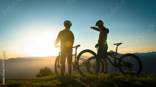 Cuadros en Lienzo Two silhouettes standing near mountain bikes, talking and observing view in the
