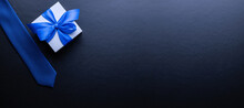 Gift Father Day. Blue Bowtie Or Tie, White Box With Bow Ribbon On Dark Background. Happy Loving Family And Fathers Day Concept.