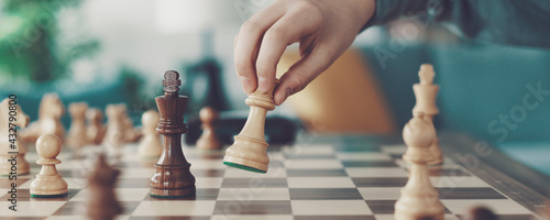Foto Boy playing chess and moving a piece