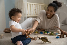 Overjoyed Loving Young African American Mother Play With Toys Block With Small Baby Daughter. Happy Smiling Ethnic Mom Have Fun Feel Playful With Little Toddler Kid Child. Parenthood Concept.