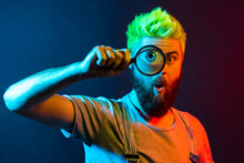 Portrait Of Astonished Young Adult Man In Denim Overalls Standing, Holding Magnifying Glass And Looking At Camera With Big Zoom Eye And Surprised Face. Colorful Neon Light, Indoor Studio Shot.
