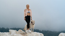 A Blonde Girl Stands With A Fawn White Labrador Dog On A Rock. Rainy Sky On The Background Of The Forest