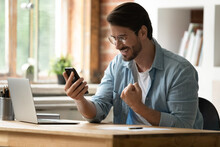 Excited Smiling Businessman In Glasses Celebrating Success, Using Phone, Looking At Smartphone Screen, Excited Young Man Reading Good News In Message, Received Money Refund Or Job Promotion