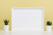 White blank wooden mock up frame and small succulent flowers on white desk with light yellow background. Front view