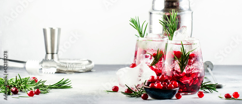 Cranberry, vodka, gin alcoholic cocktail with ice, rosemary and berries in tumbler glass. Summer long drink. Gray table background - fototapety na wymiar